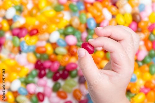 Keuken foto achterwand Snoepjes Toddler hand in Colorful candy background