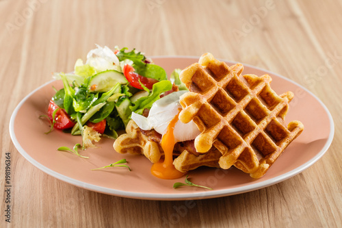 Fotografía  Savory Belgian waffles with egg poached, bacon and salad