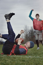 Caucasian Man On The Ground, Punching The Air, Celebrating Scoring Points With The Football In A Game Of Non-contact Flag Football.