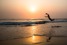 Silhouette Of Active Man Playing Frisbee On Sunset Beach