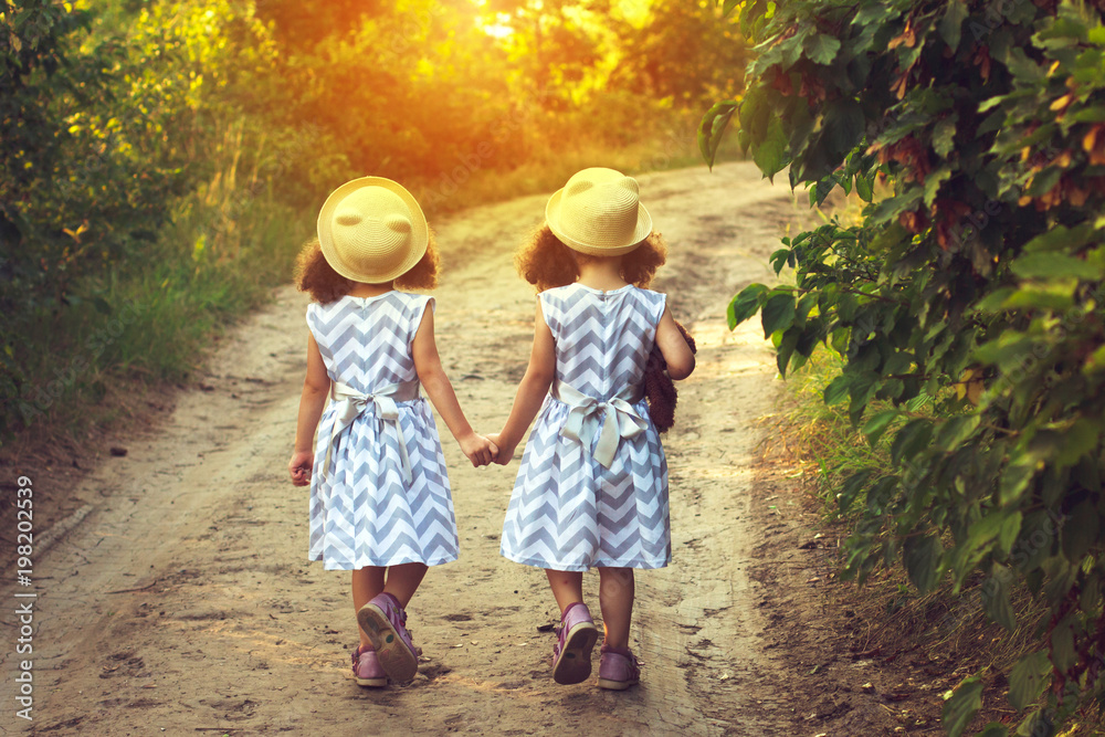 Fototapety, obrazy: Back view of two little girls holding hand and walking together in the park in vintage color tone. Future concept