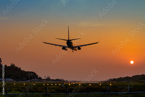 Tuinposter Vliegtuig Airplane just arrive to the airport ready to landing on the runway at sunset, transportation worldwide for passengers transmission