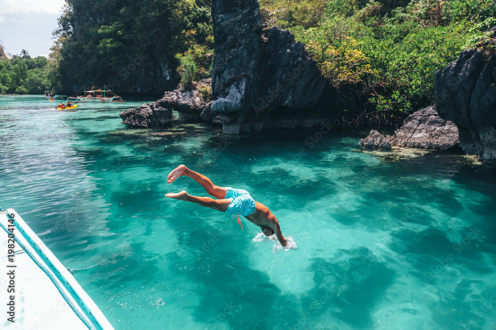 Fototapety, obrazy: Man jumping into clear sea water in Asia