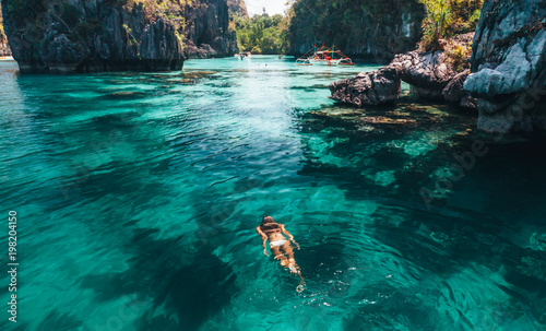 Woman swimming in clear sea water in Asia