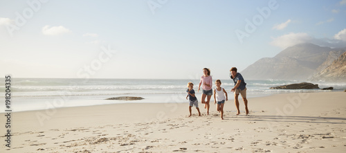 Parents Running Along Beach With Children On Summer Vacation - 198204335