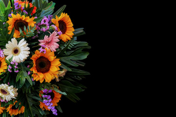 Sunflowers and Gerbera daisies flower arrangement with fern, philodendron and palm leaves the tropical foliage plants on black background.