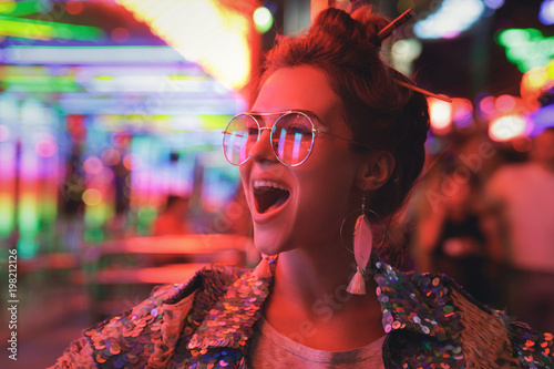 Fotografia  Woman wearing sparkling jacket on the city street with neon lights