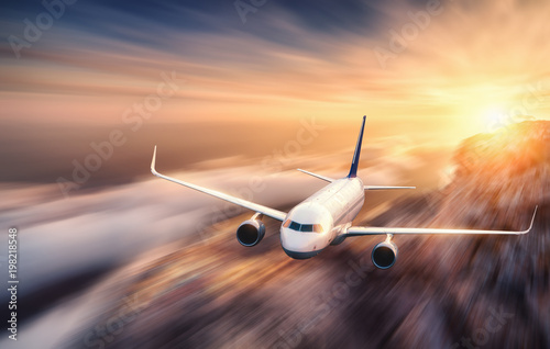 Türaufkleber Flugzeug Modern airplane with motion blur effect is flying over low clouds at sunset. Passenger airplane, blurred clouds, bright sky, sunlight. Passenger aircraft. Business travel. Commercial plane. Concept