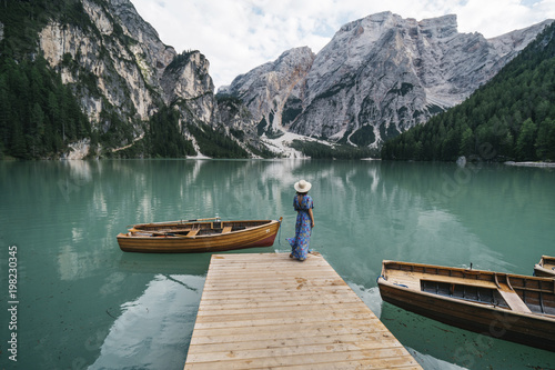 Rear view of woman standing on jetty over lake against mountain
