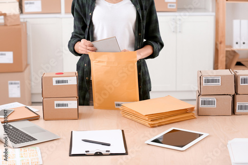 Fotografía  Young woman preparing parcel envelopes for shipment to client in home office