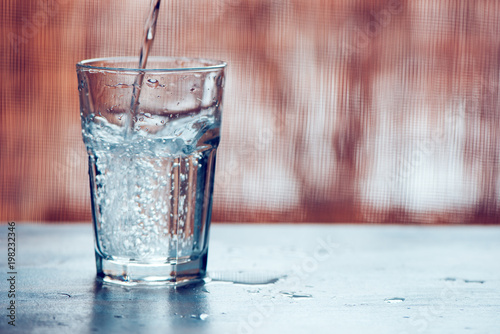 Pouring fizzy water into drinking glass