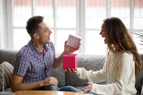 Excited young husband opening box receiving birthday present from wife, cheerful Fototapet