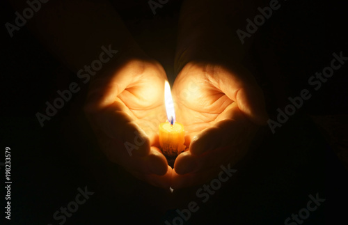 Cupped hands with burning candle.
