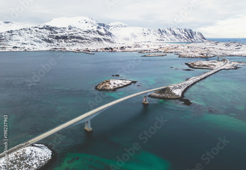 Aerial winter view of Lofoten Islands, Nordland, Norway, with fjord, road, bridge and mountains, shot from drone