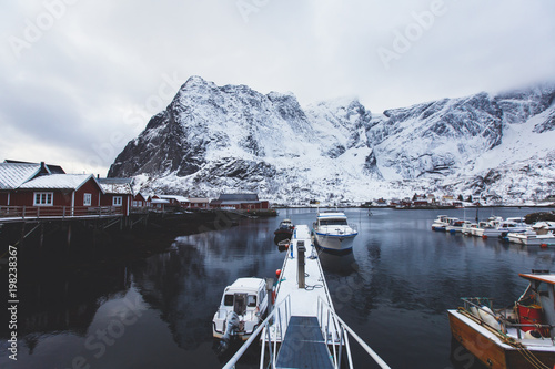 Beautiful super wide-angle winter snowy view of Reine, Norway, Lofoten Islands, with skyline, mountains, famous fishing village with red fishing cabins, Moskenesoya, Nordland