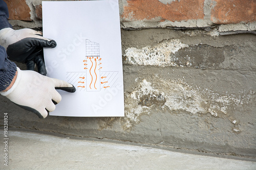 Photographie the master holds a drawing with an explanation of how the saltpeter on foundatio