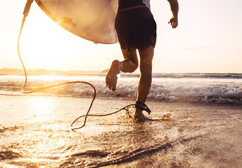 Fototapeta Man surfer run in ocean with surfboard. Active vacation, health lifestyle and sport concept image