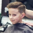 Smiling European boy in a barber shop. Ready look.