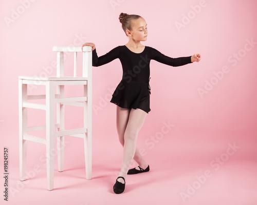 2fabd89ec1c327 Portrait of young beautiful child girl ballerina standing near armchair  practicing ballet wearing black tutu dress