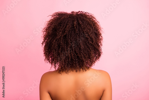 Rear, back side view of attractive, nude, curly, brunette, charming, stylish, oiled, natural, perfect hair of shirtless woman with soft skin, isolated on grey background