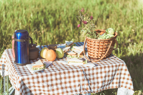 Keuken foto achterwand Picknick Appetite sandwiches, thermos bottle and basket with fresh fruits on table on the grass