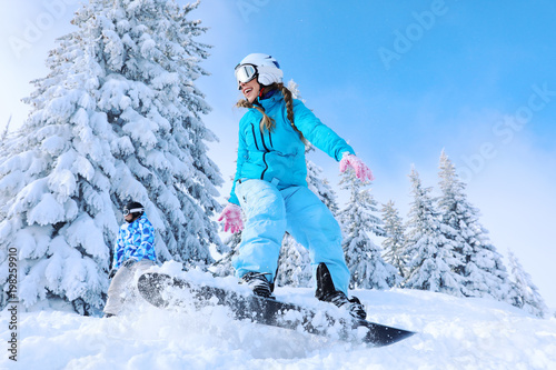 plakat Female snowboarder on ski piste at snowy resort. Winter vacation