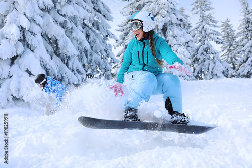 Door stickers Winter sports Female snowboarder on ski piste at snowy resort. Winter vacation