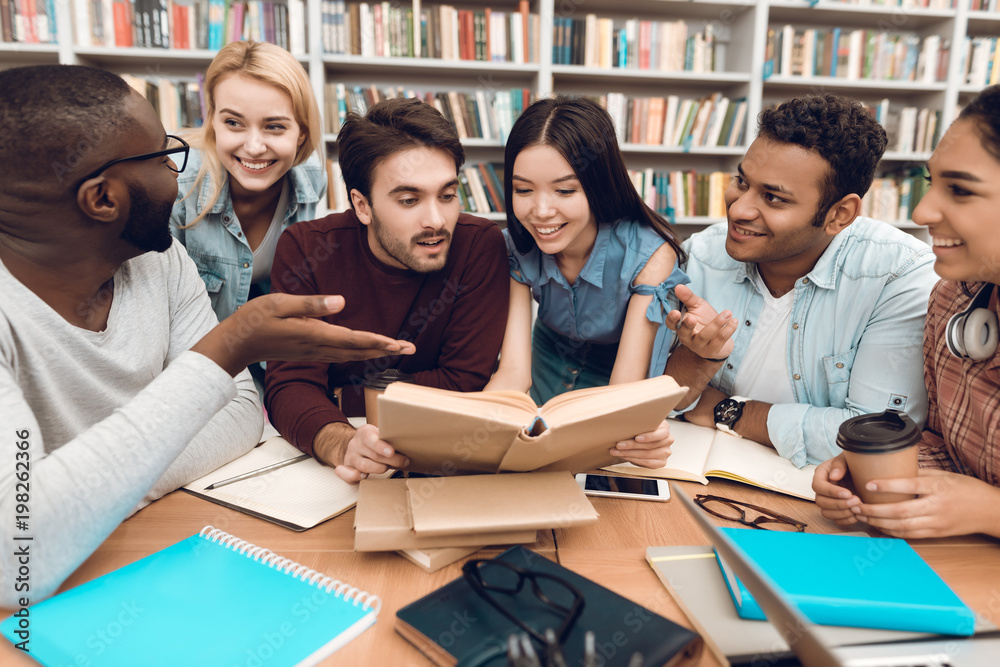 Fototapety, obrazy: Group of ethnic multicultural students discussing studying in library.