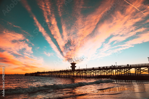 Scenic view of sea against sky at sunset along birds flying over pier