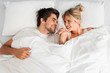 canvas print picture - Young loving couple lying on the bed, enjoying