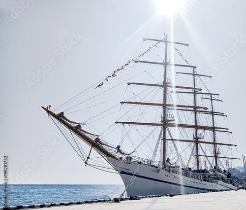 Fotobehang Art Studio White three-mast ship or frigate anchored at blue sea background