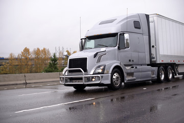 Silver big rig semi truck with grille guard transporting dry van semi trailer on rainy wet road