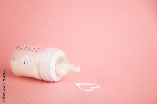 Baby milk bottle on a pink background with neagtive space. Spill