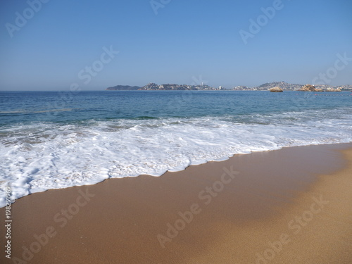 Valokuva  Panoramic view of sandy beach at bay of ACAPULCO city in Mexico and waves of Pac