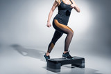 Young woman exercising on step platform on grey background