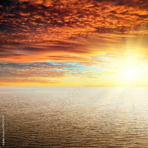 Foto op Aluminium Strand red sunset in clouds over sea