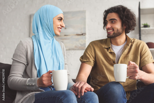 Fotografia smiling muslim couple holding hands and holding cups of coffee at home