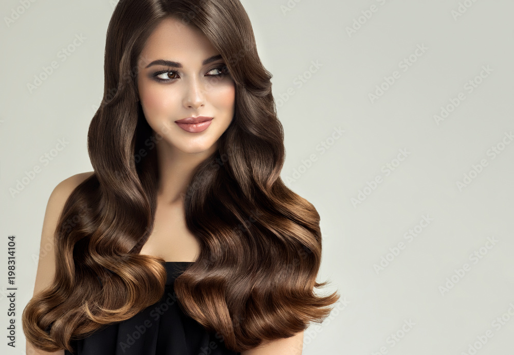 Fototapeta Brunette  girl with long , healthy and   shiny curly hair .  Beautiful  model woman  with wavy hairstyle   .Care and beauty