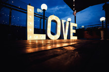 Word Love From Big, Letters With Glowing Light Bulbs On A Dark B