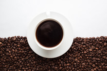 Coffee Cup On Half Coffee Beans And Half White Background