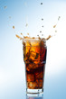 Ice splashing on a glass of a Cola drink