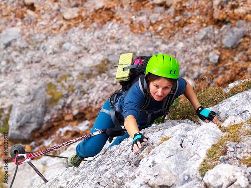 Klettersteig Germany : A young brave girl in green helmet going via ferrata seeben