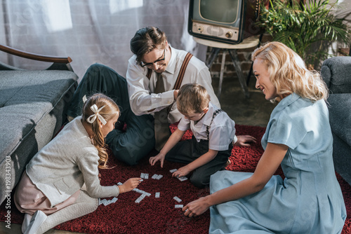 Photo happy family with two children playing dominoes together at home, 1950s