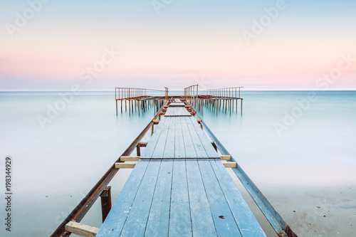 Long esposure view of a old jetty in a calm sea with gentle sky, soft colors