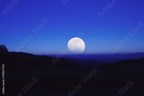 Staande foto Donkerblauw Full Moon from the mountain silhouettes landscape.