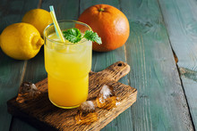Refreshing Lemon Orange Drink With Ice And Mint On A Rustic Blue Table With Backlighting. Summer Cooling Fruit Drink Close-up. Place For Text.