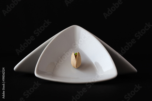 Spoed Foto op Canvas Klaar gerecht White triangular ceramic bowls with pistachio nut.