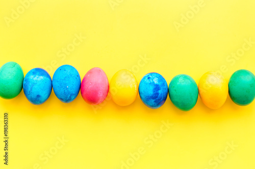 Colorful easter eggs with blossom branch on yellow background top view mockup