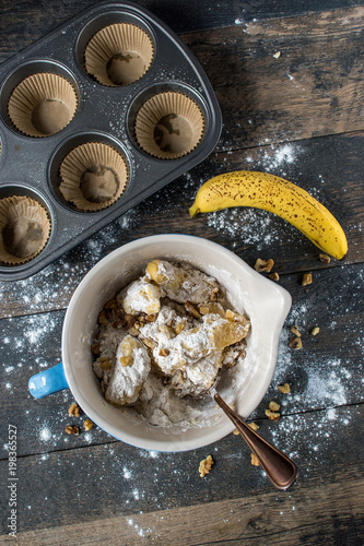 Fotografie, Obraz  mixing ingredients from scratch for banana nut muffins in mixing bowl top view