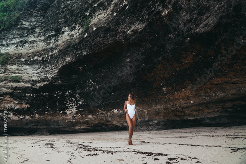 Cadres-photo bureau Jogging amazing girl in a white swimsuit with a beautiful sports body walking and posing on a white sand beach. A tanned young woman with curly hair is resting and sunbathing. Charming model posing near the